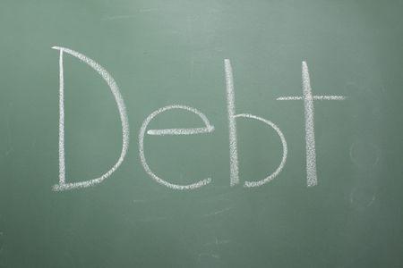 The word debt written on a chalkboard.