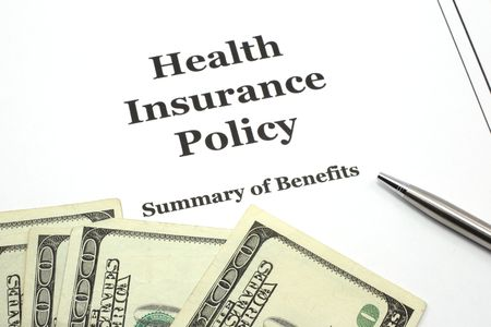 insurer: A health insurance policy with a pen ready for signing surround by cash in hundred dollar bills. Stock Photo