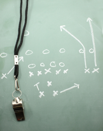 A football diagram on a chalkboard showing the sweep with a coaches whistle. Stock Photo