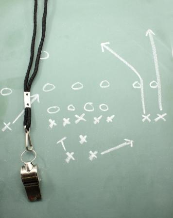 Een diagram van de voet bal op een school bord toont het vegen met een fluitje coaches.  Stockfoto