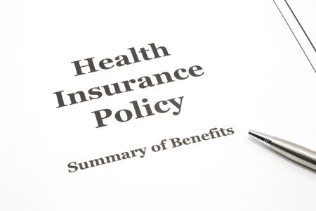 policies: A health insurance policy with a pen ready for signing the papers. Stock Photo