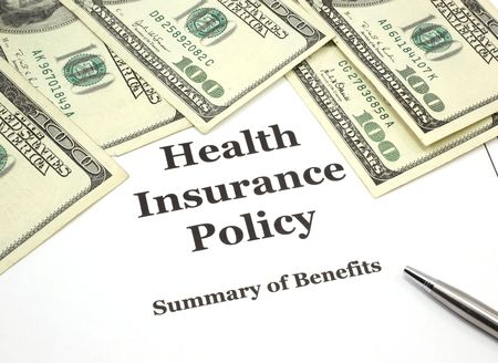 health insurance: A stack of one hundred dollar bills around a health insurance policy and a pen.