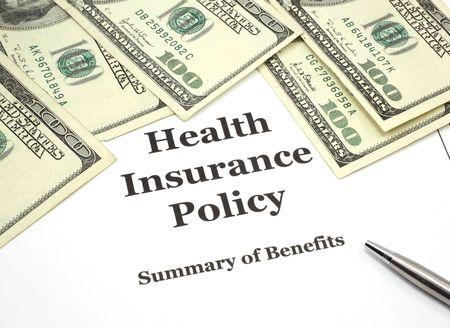 Een stapel van honderd-dollarbiljetten rond een ziektekostenverzekering beleid en een pen.