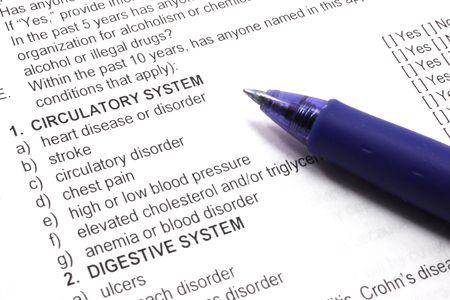 feltételek: Health insurance medical questions on an application with a pen.