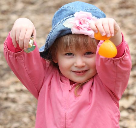 A happy little girl in pink with a hat opens an orange Easter Egg to get the candy inside during egg hunt. photo