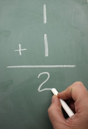 equals: A hand is writing one plus one equals two on a blackboard.