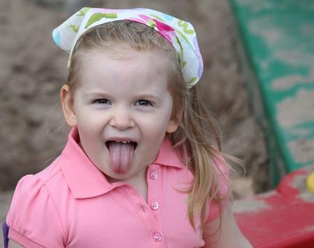 彼女の頭にスカーフとのピンクの服を着ている間に彼女の舌を突き出てサンド ボックス内でかわいい女の子。