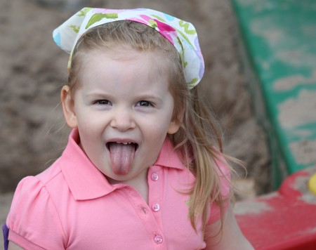 A cute little girl in a sandbox sticking her tongue out while dressed in pink with a scarf on her head.