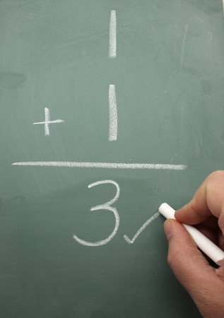 equals: A hand marking a math problem wrong that shows one plus one equals three on a blackboard.