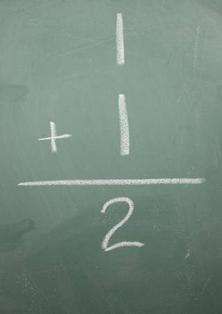 equals: One plus one equals two math problem on a blackboard.