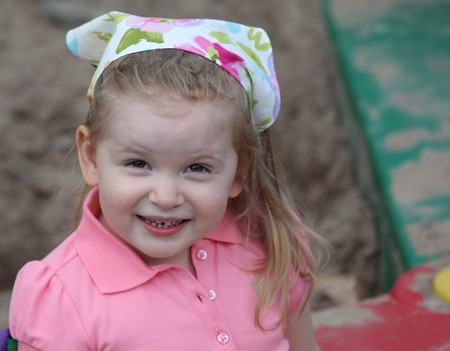 A Cute Girl Smiling in Sandbox with a Scarf on Head dressed in pink. photo