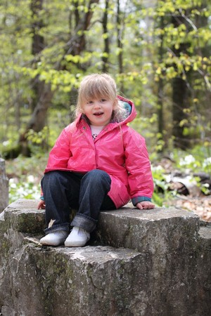 A happy little girl in pink sitting on a rock and smiling.