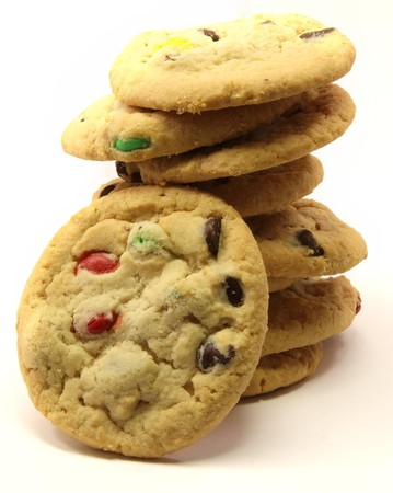A stack of chocolate candy cookies with one cookie in front.