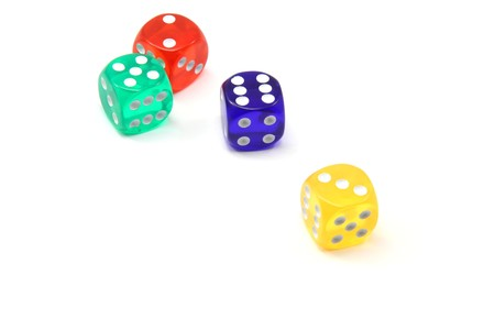 A green, red, blue, and yellow colored dice spread out after a roll. photo