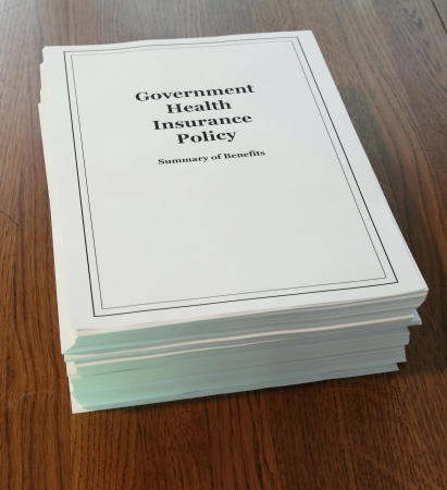 policies: Health care reform government policy summary of benefits on a wooden desk.