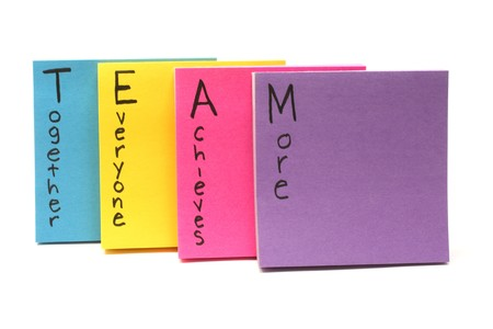 achieves: Colorful sticky note pads spell out Team together everyone achieves more. Stock Photo