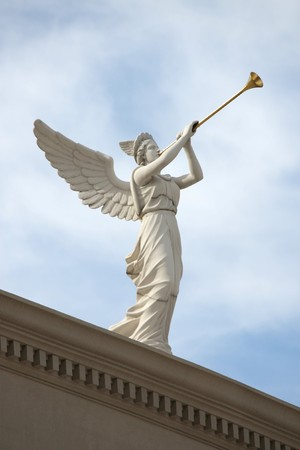 A trumpeting angel on top of a building against a blue sky.