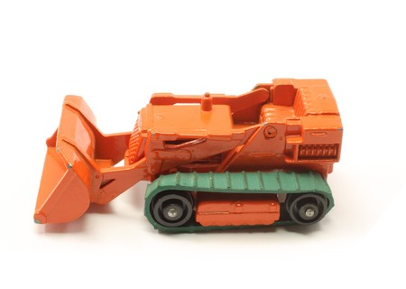 A toy orange vintage bulldozer on a white background. photo
