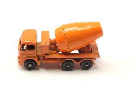 A vintage orange toy cement mixer on a white background. photo