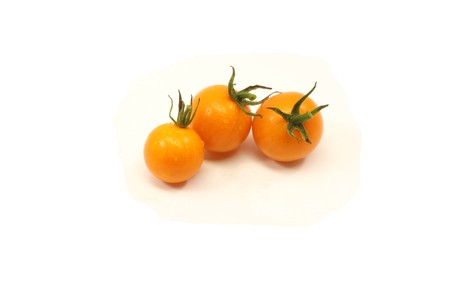 Three yellow cherry tomatoes fresh from the garden and ready for eating sprayed with water while cleaning. Stock Photo - 7848263