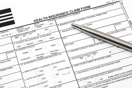 filled out: A health insurance claim form with a silver pen ready to be filled out for manual submission to an insurance carrier.
