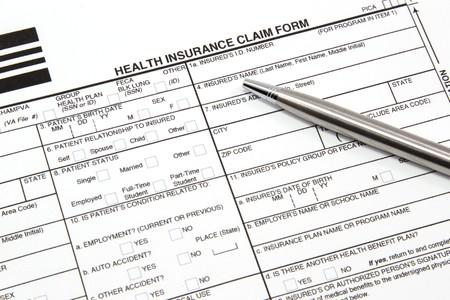 Een ziekte kosten verzekering vorderings formulier met een zilveren pen klaar om te worden ingevuld voor handmatige ing aan een verzekerings maatschappij.