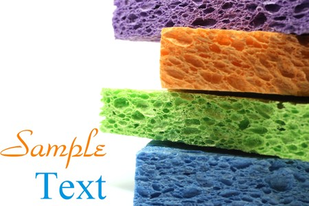 Purple, blue, orange, and green colorful sponges on white back background with copy space.  Macro with extremely shallow depth of field. Stock Photo