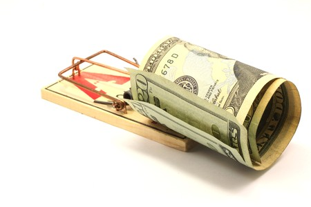 baited: Twenty dollars bills baited in a set mouse trap showing money trap concept.