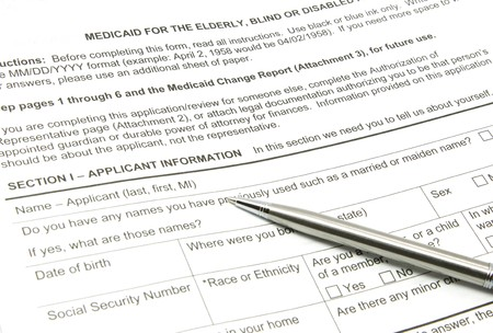 filled out: A Medicaid application ready to be filled out with a silver pen.