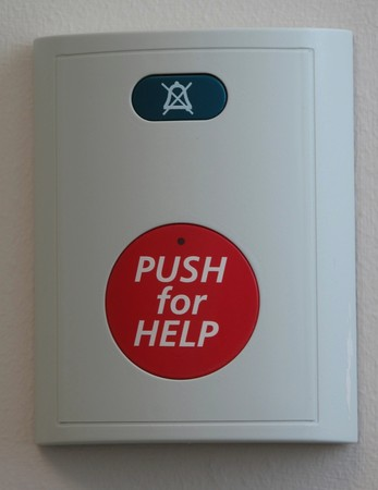 Photograph of a red push for help emergency button located in a white box photo