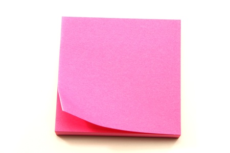 A pink sticky pad note with the end curled up on the top sheet. photo