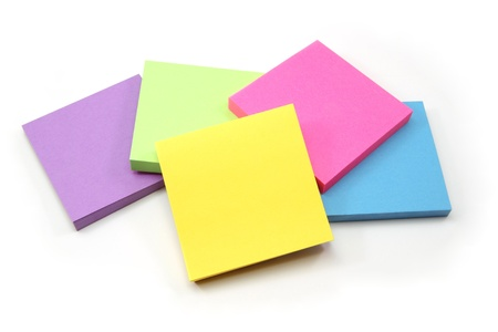 A colorful array of sticky note pads including purple, pink, green, yellow, and blue. photo