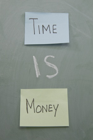 Time is money written on a chalk board with chalk and colorful paper sticky notes.