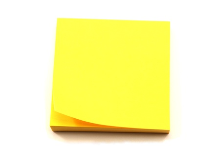A stack of yellow sticky note pads with a corner turned up. photo