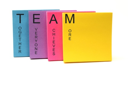 achieves: TEAM together everyone achieves more concept on an array of colorful sticky notes.