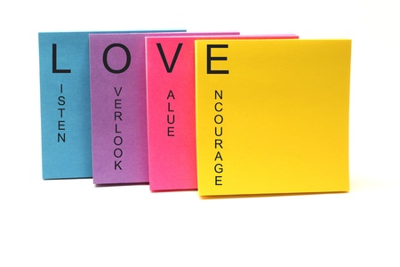 LOVE listen, overlook, value, encourage concept on an array of colorful sticky notes.