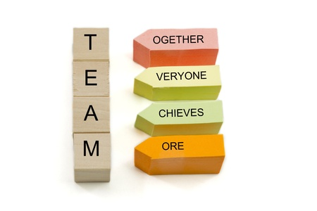 achieves: TEAM, together everyone achieves more spelled out on wooden blocks and colorful sticky notes. Stock Photo