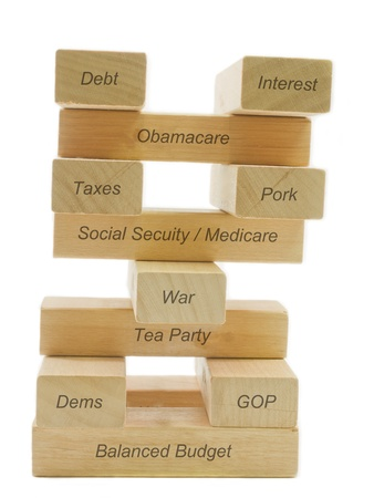 A concept of balancing the budget showing different factors balancing on wooden blocks including dems, gop, taxes, pork, tea party, war, medicare, social security, healthcare, and interest.