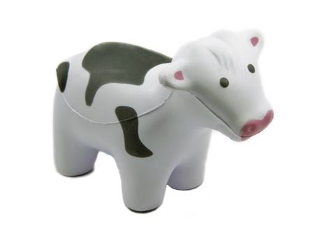 A soft toy black and white cow standing sideways.