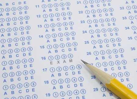 A blue bubble or scantron sheet with a number two yellow pencil.  The word Exam stands out in the middle of the answer sheet. Stock Photo