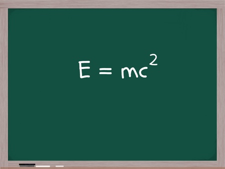 squared: E=MC squared written on a blackboard with white chalk and an eraser in the corner. Stock Photo