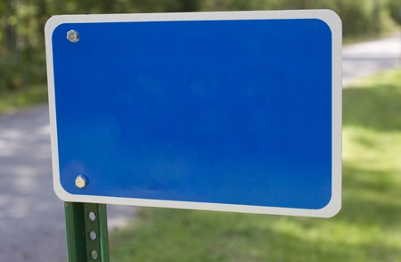 A blank blue fire number or street address sign on a green post showing a rural road and grass behind it. Imagens