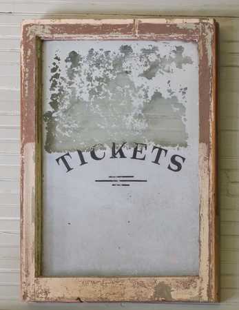 An antique Ticket window sign from an old train depot with a cracked border and aged glass backing.