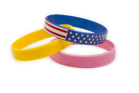 Three cause bands arranged together with a yellow band, a pink band, and an American red white and blue wrist band.