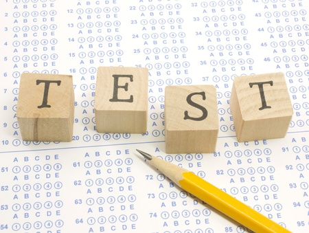school exam: Wooden blocks spell out TEST on a blue bubble or scantron sheet with a number two yellow pencil.