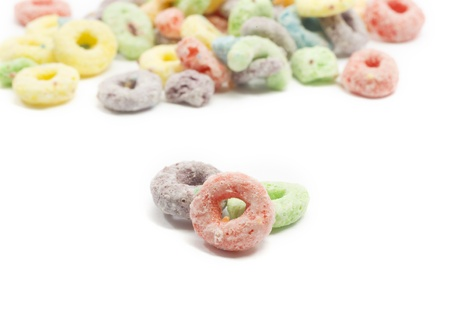 A close up of a fruit circle o cereal pieces in a macro shot with selective focus to blur out background cereal.