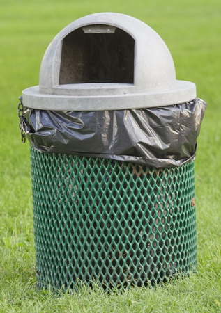 A green and gray topped garbage can in the park with a black plastic bag in it.