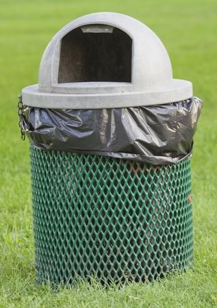 A la basura encabezó verde y gris puede en el parque con una bolsa de plástico negro en ella. Foto de archivo - 11267157