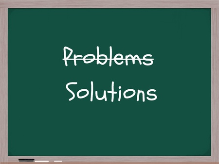 problems solutions: A blackboard with the word Problems crossed out and Solutions written under it in white chalk with an eraser on the bottom. Stock Photo