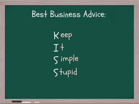 A chalkboard with the words Best Business Advice KISS acronym Keep It Simple Stupid. Foto de archivo